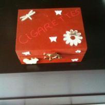 Boîte à cigarettes rouge et ses décorations blanches