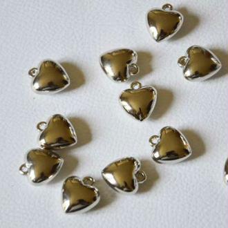 Petits coeurs en métal argenté  à suspendre. Vendus par 6