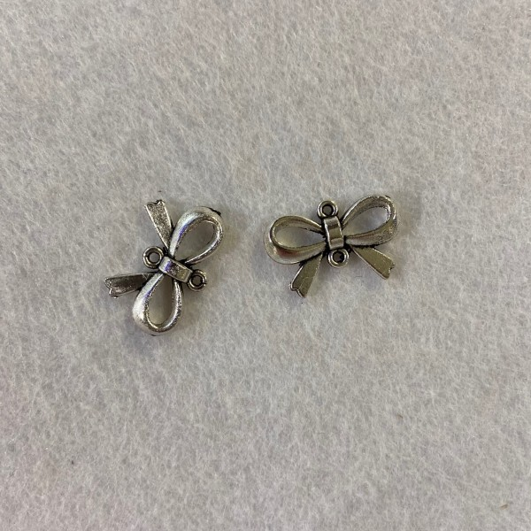 Deux breloque en forme de nœuds métal blanc - Photo n°1